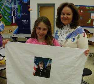 4th grader, Megan Wallace holds her pillowcase with a picture of her mother, who is deployed, as she stands with Joan Saunders, the guidance counselor at Pembroke.
