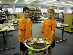 Second-graders Jacob Faison and Caden Templeton carry books for the Dey Book Swap.