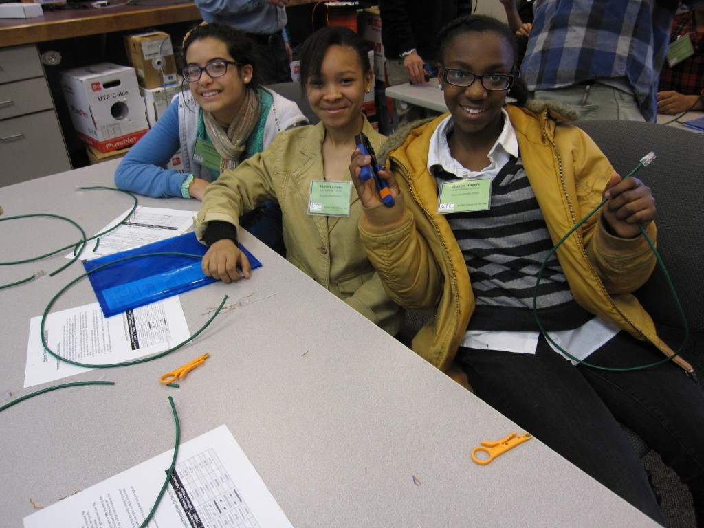 Isabella Arroya, Kambri Adams and Queen Haggie from Corporate Landing Middle School are working with fiber optic glass in Telecommunications.