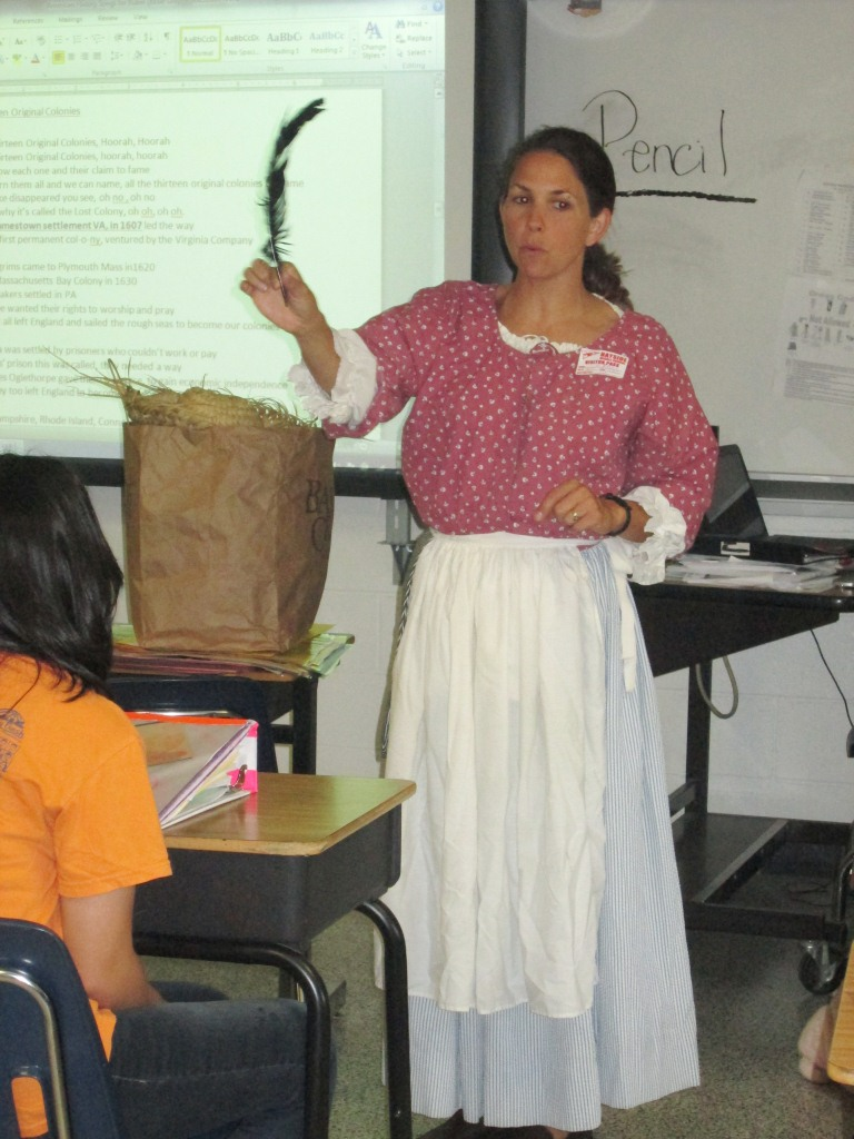 Cindy aitken in the role of miss elizabeth shows students a writing