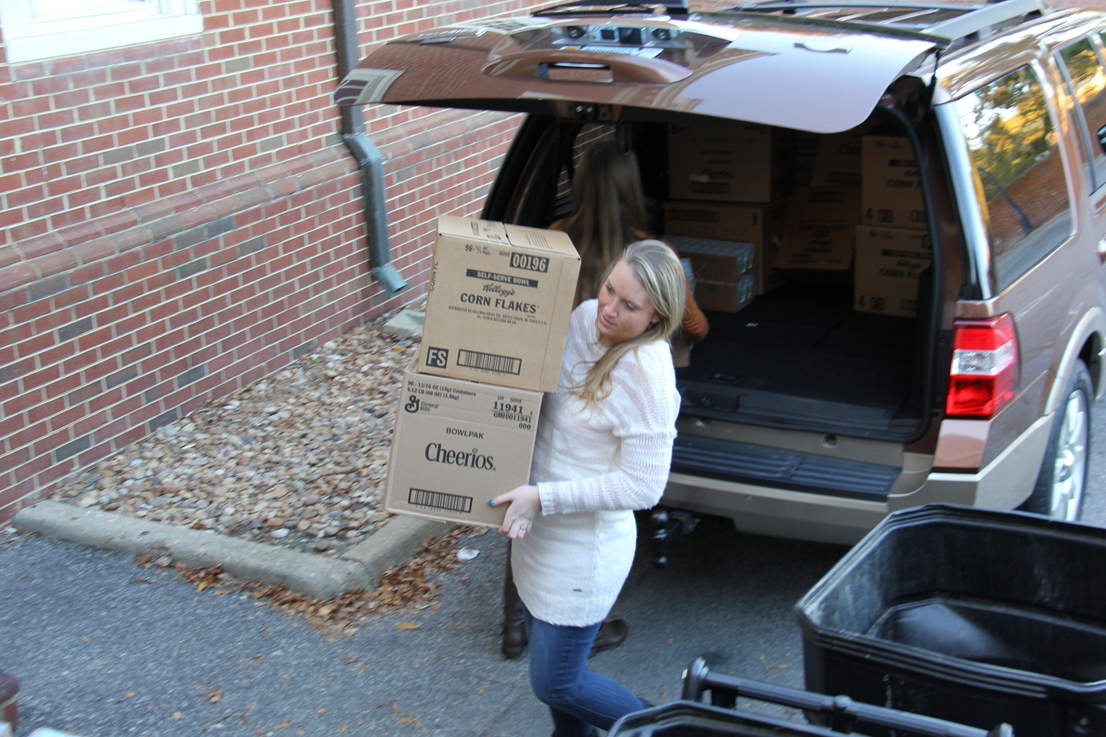 Shelby Wilkins unloads boxes of food to be donated to the Beach Bags program.