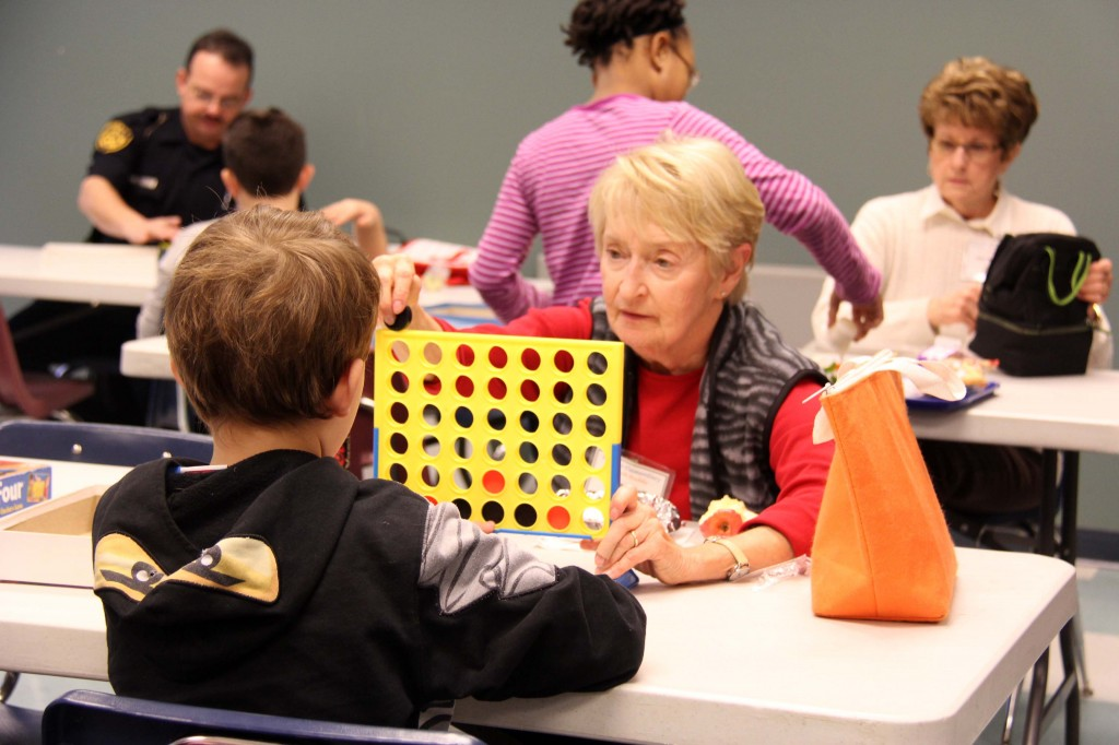 Retired nurse Norma McNelly challenges her lunch buddy to a game of Connect Four.
