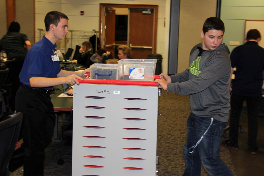 ATC students set up an extra cart to distribute laptops to the dozens of Technology Academy participants.