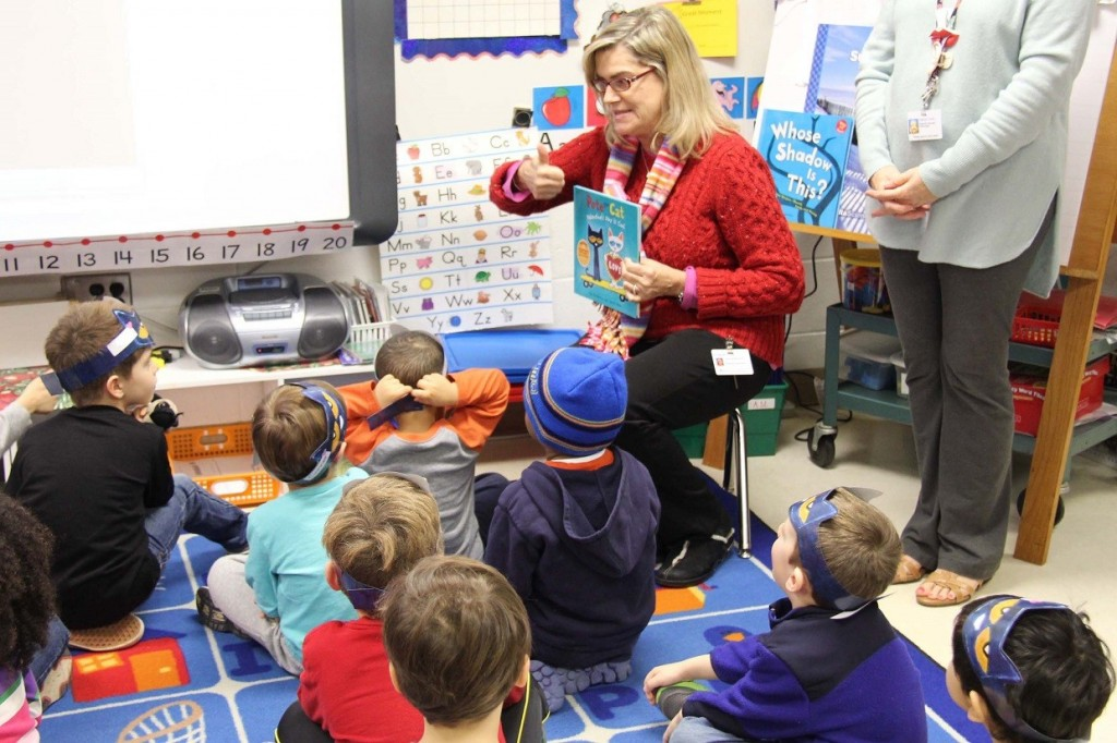 Reading specialist Annette Conley shows children the book they get to take home.