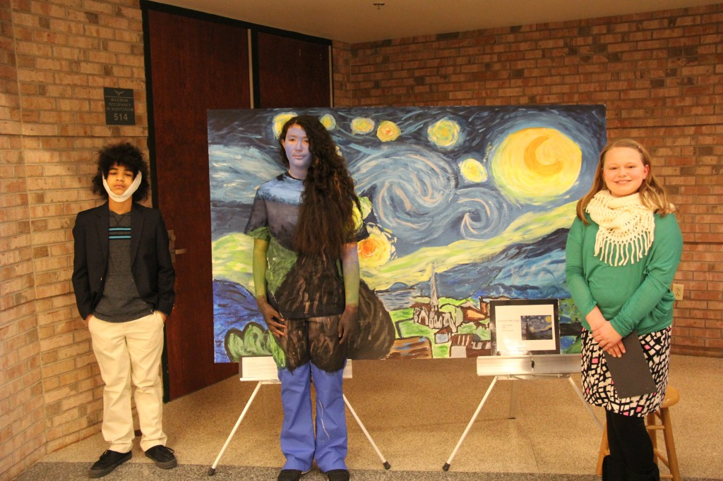 Van Gogh stands next to Starry Night wearing a head bandage because the group wanted to represent the artists severed ear.