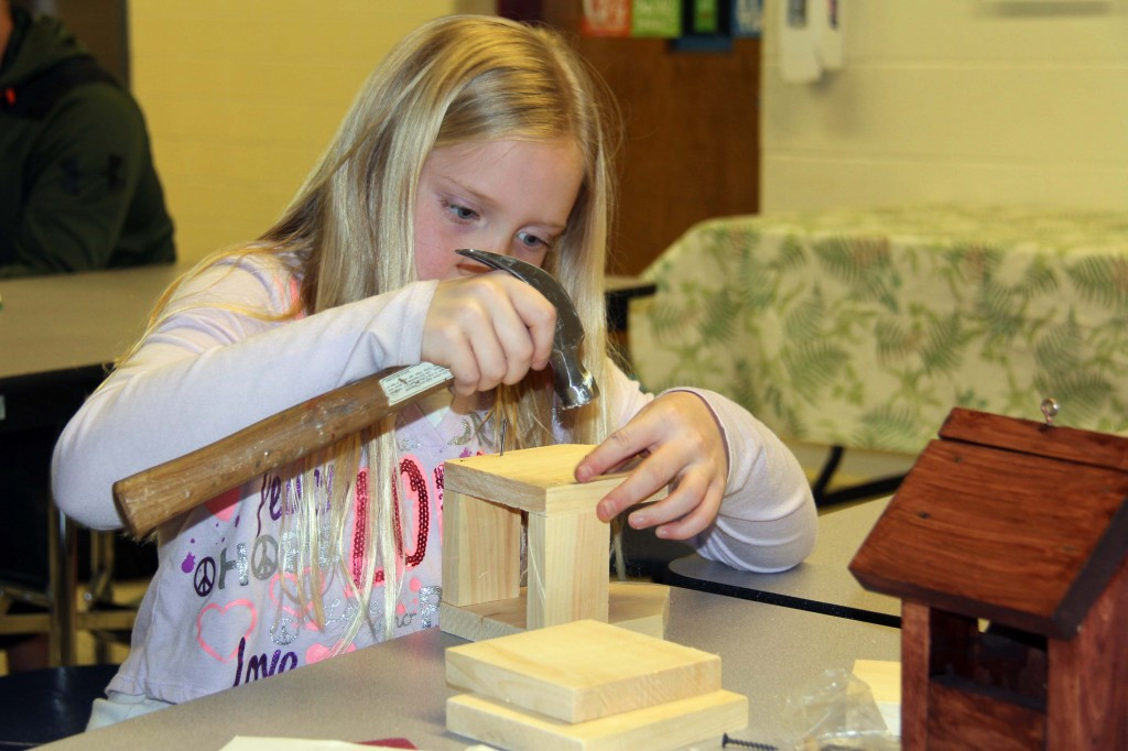 Latta hammers together pieces of a birdhouse kit.