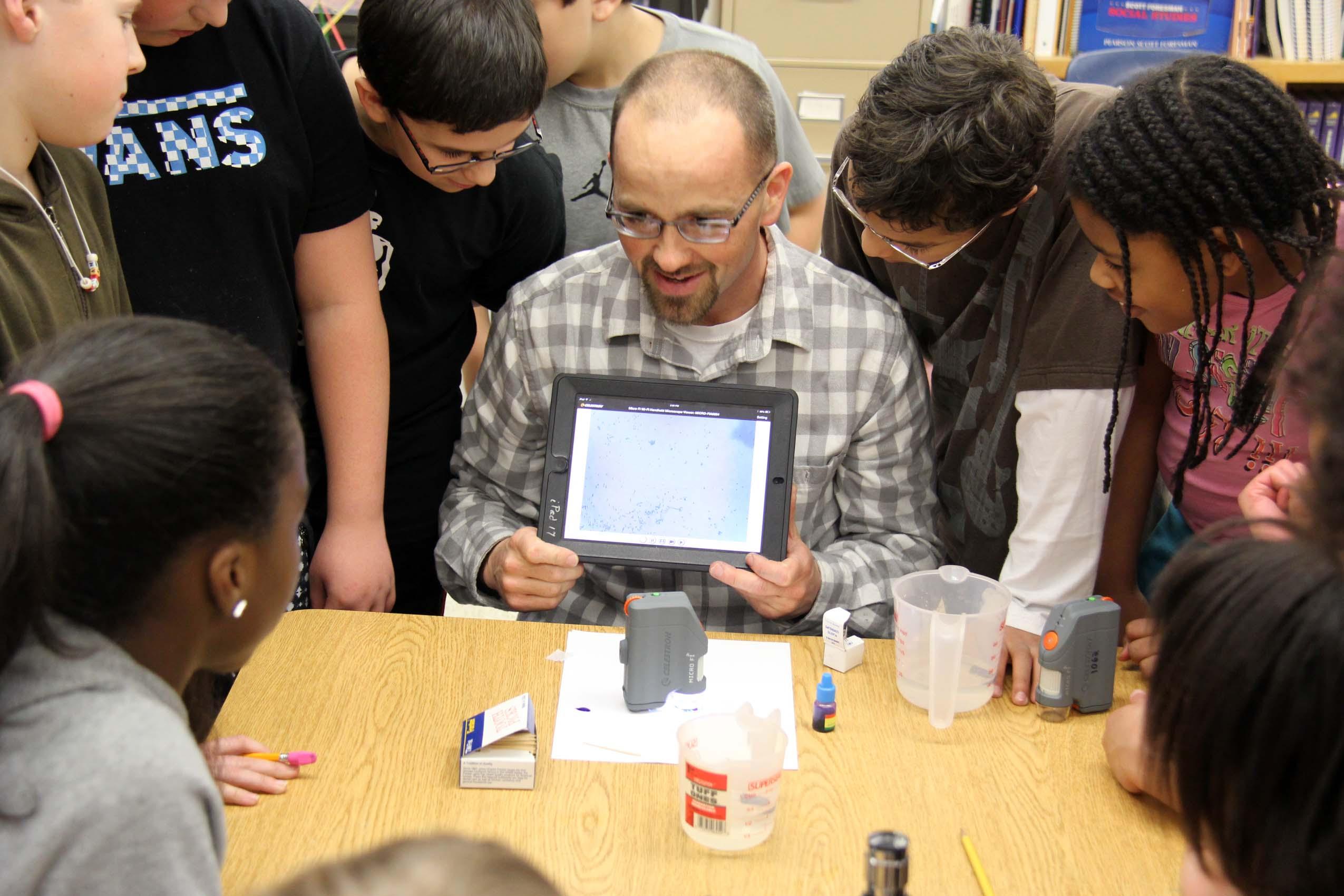 Fifth-graders view their teacher's cells through an iPad display.