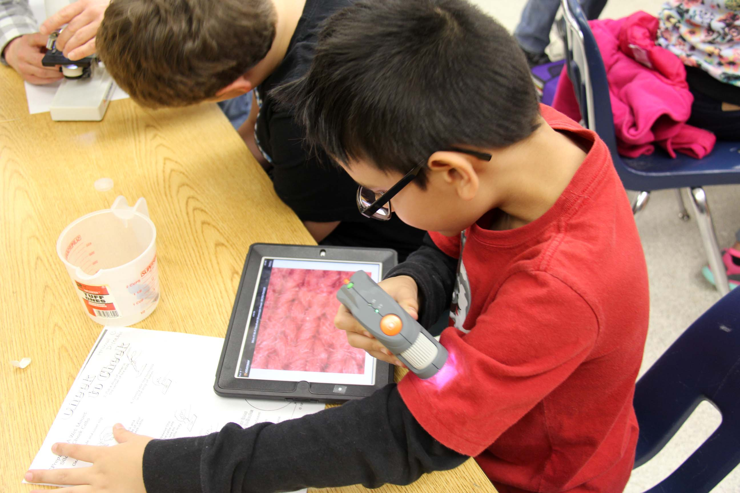 A fifth-grader uses a Micro Fi for a close-up view of the fabric in his shirt.