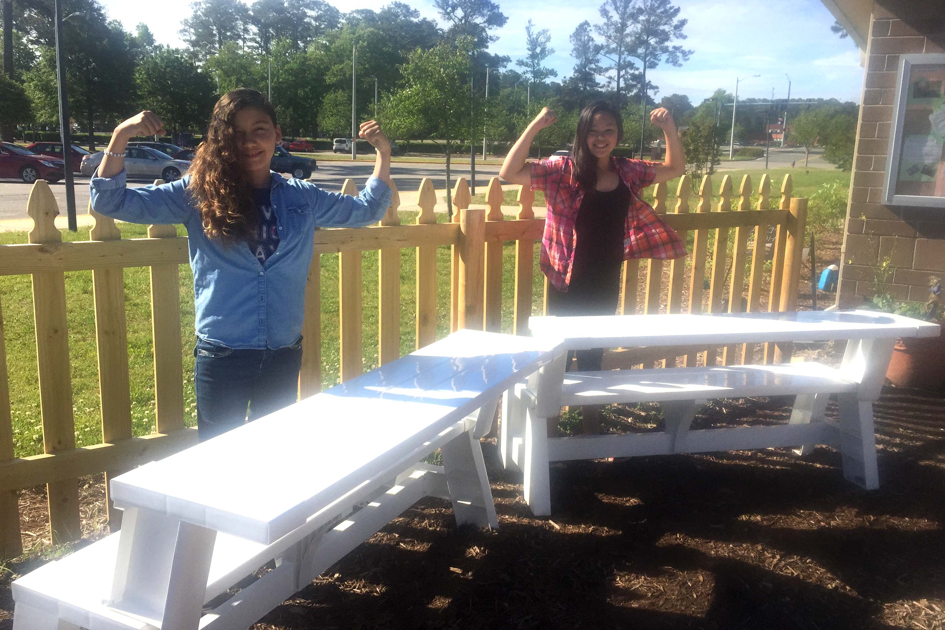 Ramirezhuezo and Coss stand by the benches they assembled.