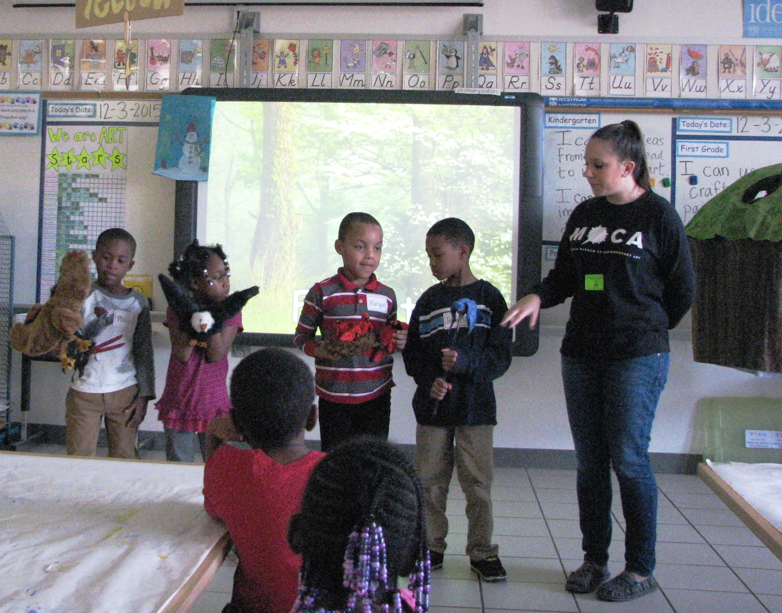 First-graders Philip Thomas, Ramyah King, Marquis Day and Jordan Davis work with the outreach educator Melanie Columbus to show animals in the forest.
