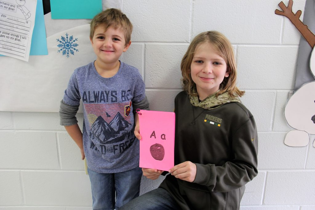 Two students showing A letter card