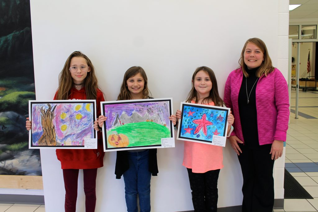 three students displaying their artwork