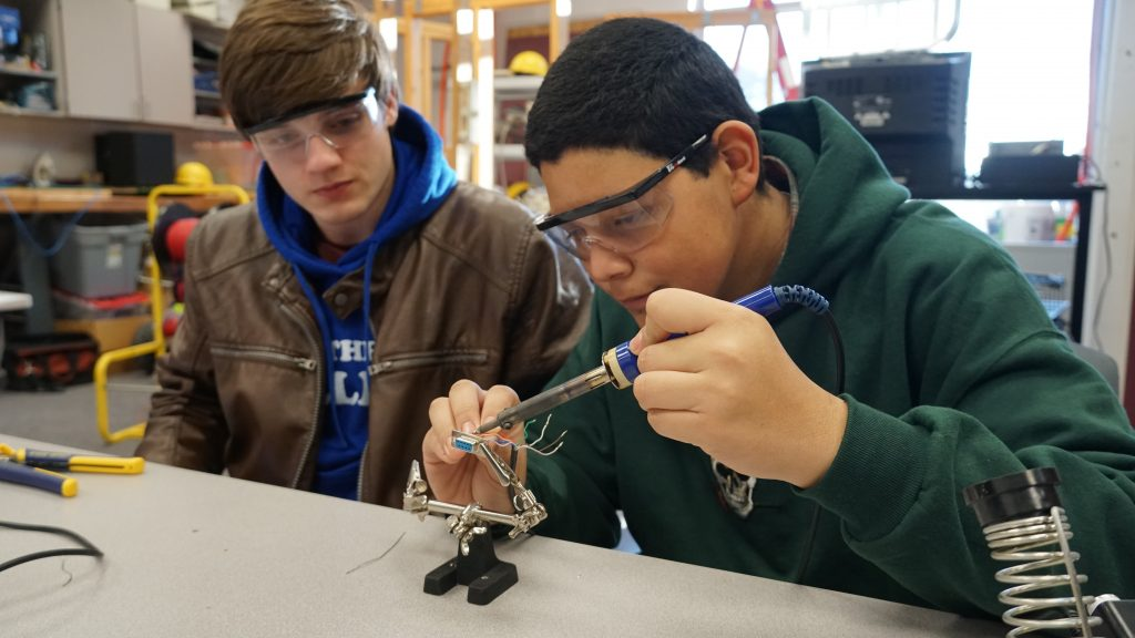 At the Advanced Technology Center, John Gras and Roberto Sandoval soldered wire to a ninepin connector.