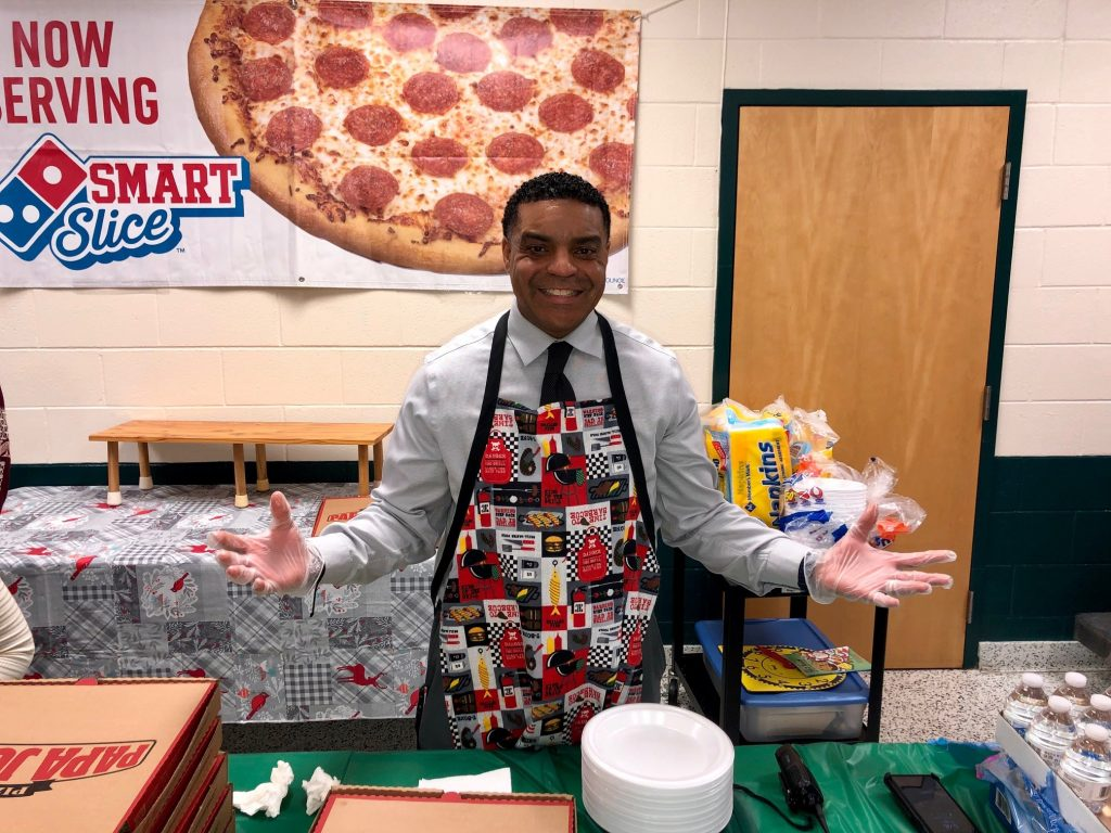Kempsville Meadows Elementary School Principal Mikelle Williams serves pizza during Literacy Night.