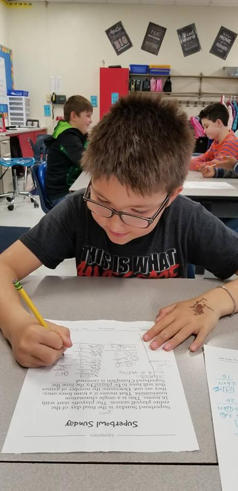 Third-grader Miles Heitsenrether at King's Grant Elementary School worked to solve a Super Bowl math exemplar.