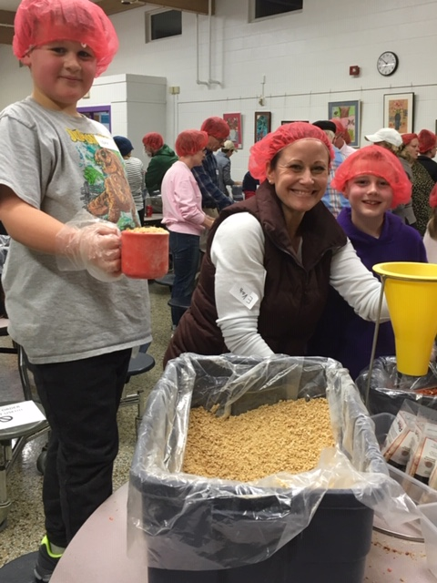 Luxford Elementary School Principal Danielle Colucci and son Alec participated in the Rise Against Hunger event, packing over 21,000 meals for people in need worldwide.