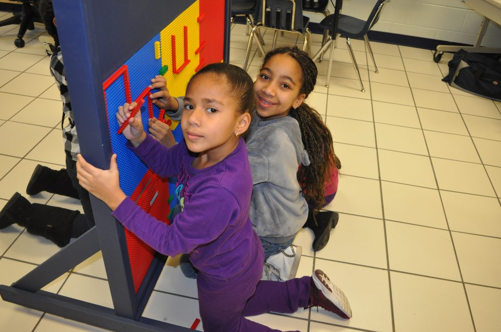 Amira Lail and Ariana Velazquez get creative as the first students to work with Newtown Elementary School's new mobile LEGO Wall.