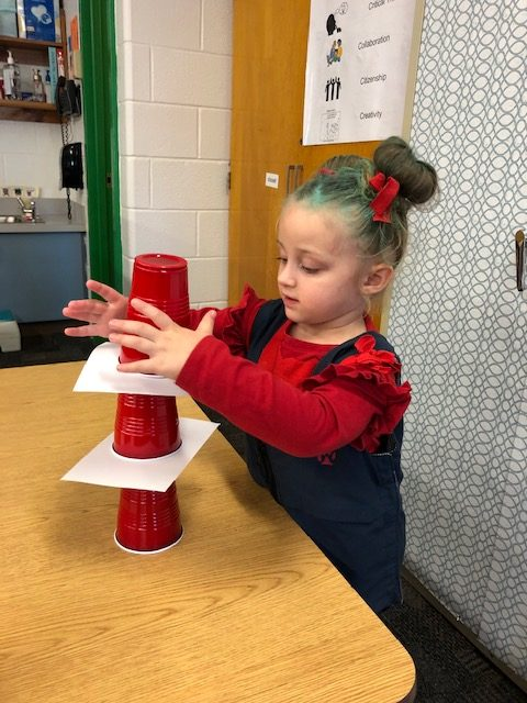 Green Run Elementary preschooler Kayleigh Plourde stacks Dr. Seuss hats while dressed as Thing 1 in honor of Dr. Seuss Day.