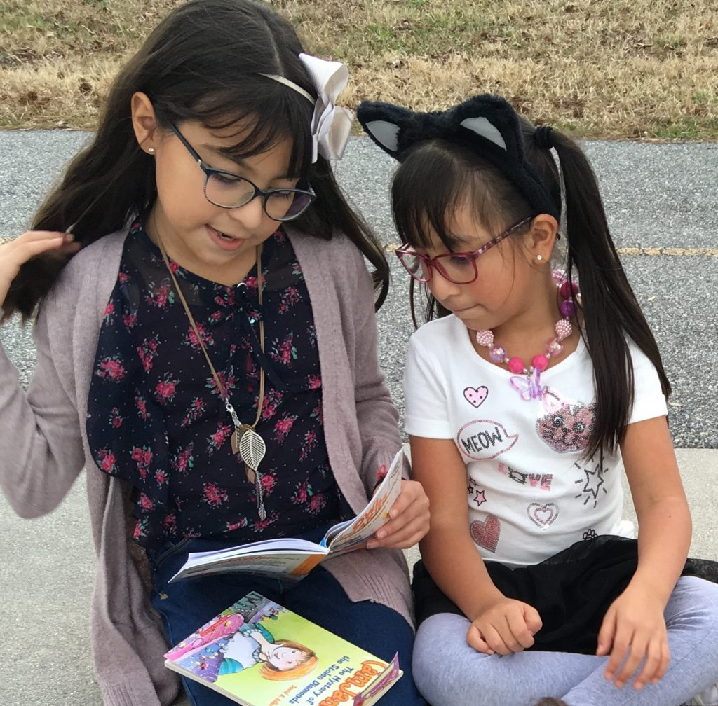 Kindergartener Sofie Amador and her second- grade reading buddy/sister, Denise Amador enjoyed a great book and beautiful weather at Luxford Elementary.