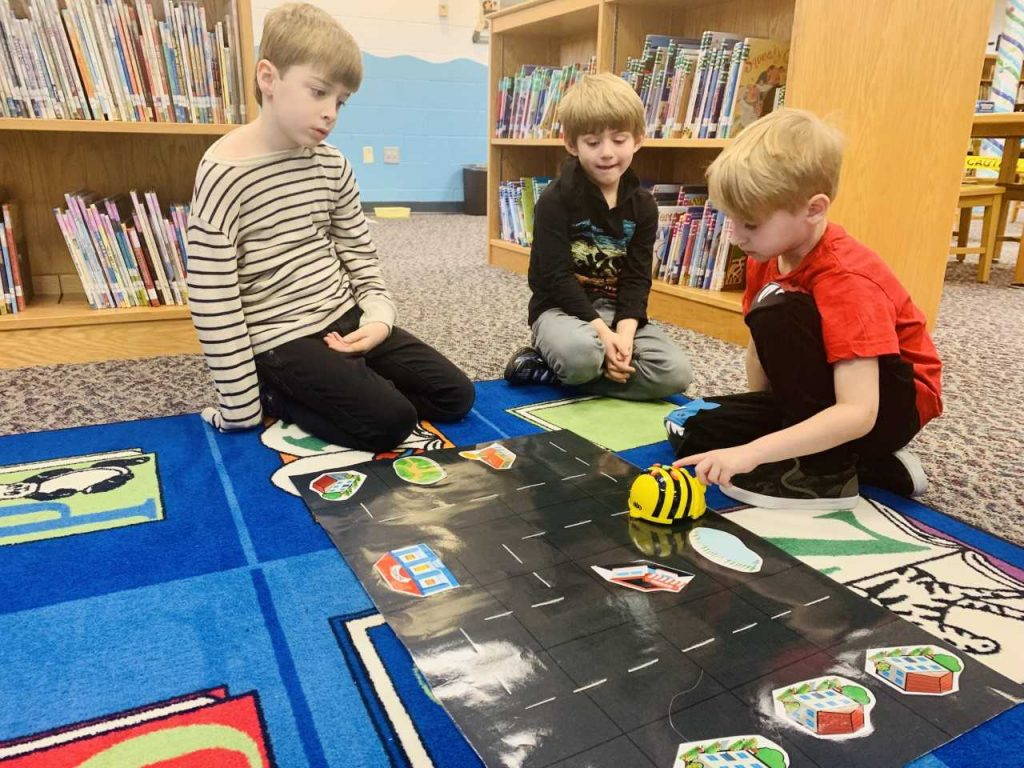 Malibu Elementary School students Ryan Vaughan, Evan Barbini and Grant Turpin School practice coding the BeeBots during a library lesson about maps