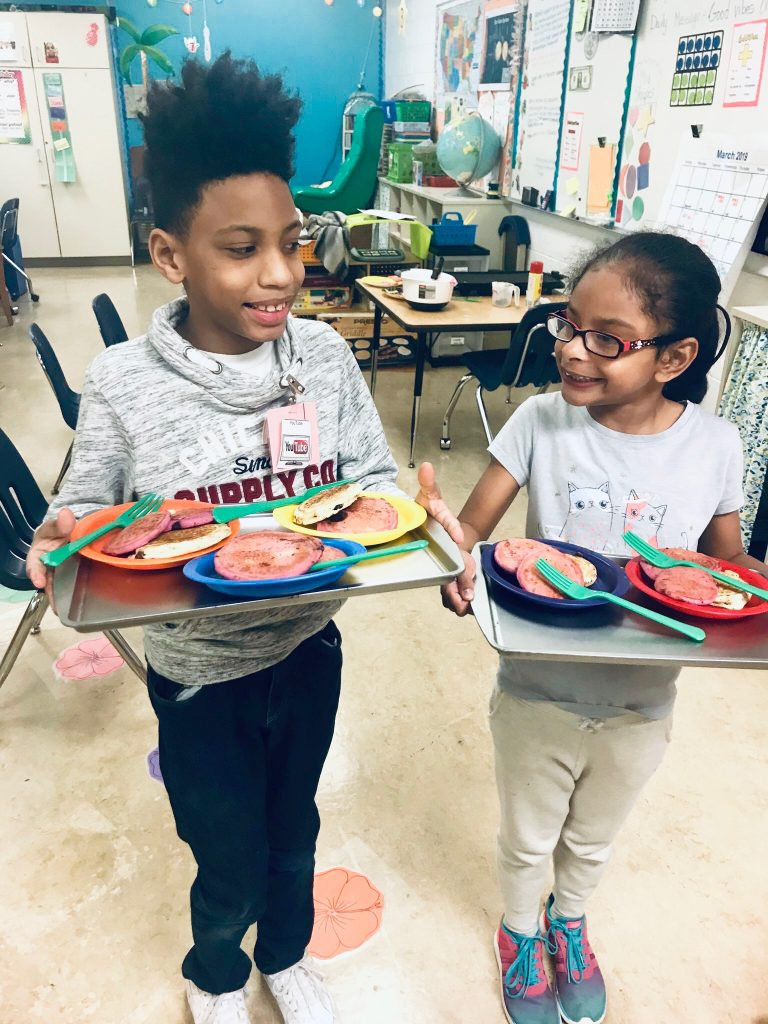 Kempsville Elementary School studentss Josiah Faulks and Karissa Ruiz proudly presented their purple pancakes to the office staff for Mardi Gras.