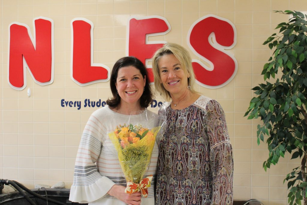 "Principal Jill Barger presented parent volunteer Kelly Campbell with a bouquet to celebrate her being named North Landing Elementary School's, ""Volunteer of the Year."""