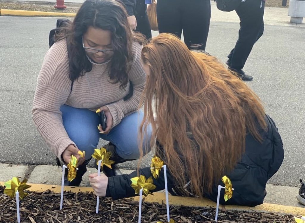 Seniors Anis Mohammad and Hannah Morfeld place their legacy pinwheels in the ground during advisory at Ocean Lakes High School.