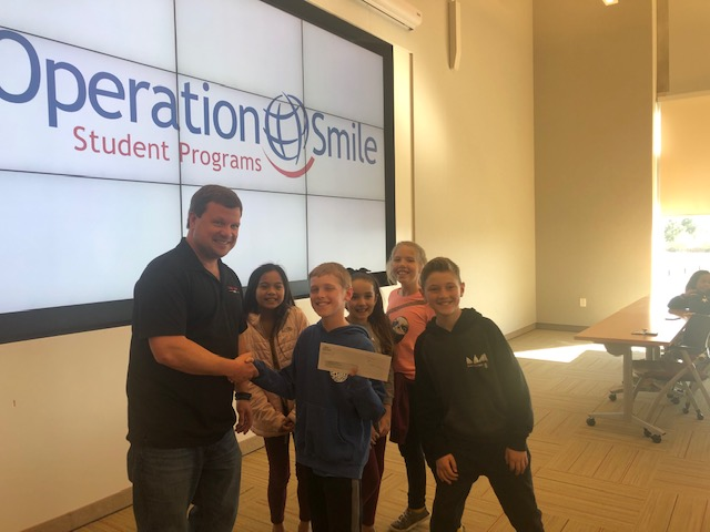 Princess Anne Elementary SCA members presented proceeds from a Smilegram fundraiser, a check for $500, to Operation Smile Student Programs Associate, Pete Hansen.