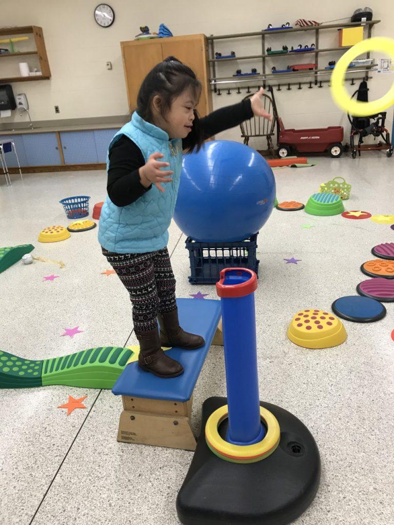 "Rosemont Elementary School's Allison Sam tosses ""Saturn's rings"" into a ""black hole"" target."