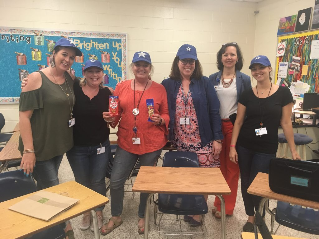 "Dawn Kramer, assistant principal at Lynnhaven Middle School, celebrated the 8th grade English teachers by giving them a ""homerun"" package with ""superstar"" baseball hats and crackerjacks for their work on raising their student's test scores."
