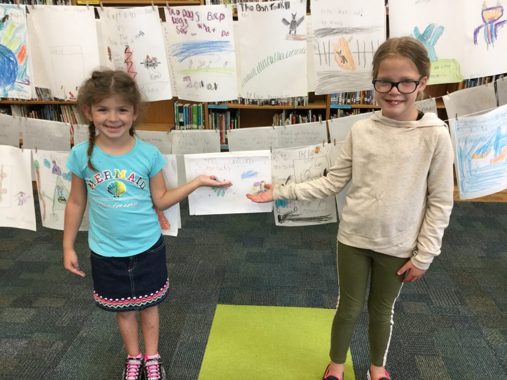 Princess Anne Elementary first graders, Charlie Thurbon and Sydney Techanchuk, chuckle at the book covers created by first graders in celebration of National School Library Month.