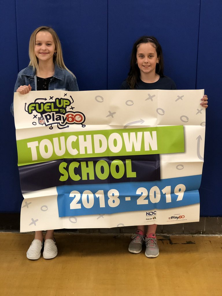 Lily Enlow and Payton Warnock proudly display the banner from Fuel Up to Play60, which names Red Mill Elementary as a Touch Down School. Payton will also help represent the state of Virginia as a FUTP60 student ambassador in Cleveland, Ohio this summer.